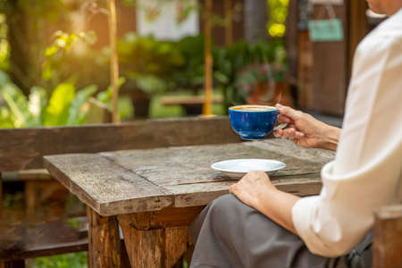 Mature woman drinking coffee while sitting at wooden table outside coffee shop on morning. relaxation , lifestyle concept