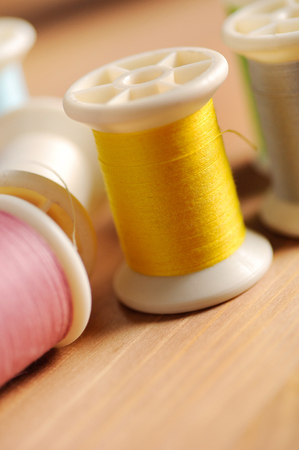 sewing cotton: yellow thread on wood table shallow depth of field (soft focus)