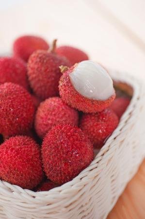 lechee: stack fresh lychee in basket on wood floor