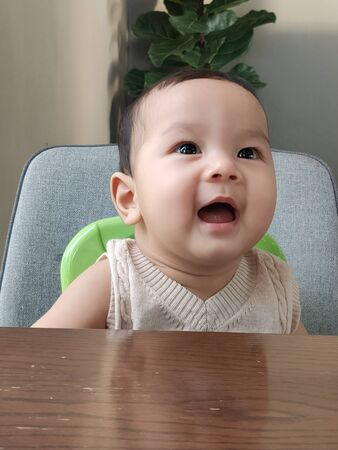 Asian baby laughing, Wow face sitting on a chair