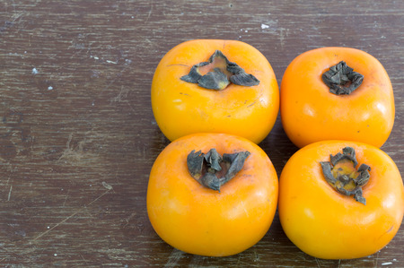 Ripe persimmons on  dark brown wooden background for work decoration