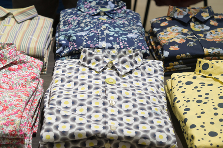 Stacking shirts with colorful pattern are on sale in orderly piles in department store, colorful shirts are stacking in order on sale in a shop Фото со стока
