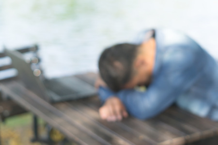 A man is taking a break by sitting with falling his head down on the desk after using laptop in a public park, blurred picture