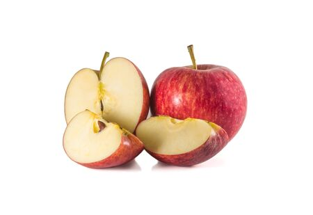 A full ripe fresh red apple with its half and two small pieces is isolated on white background. An isolated full ripe fresh red apple with its half and two small pieces on white background