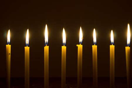 several glowing lights of candles brighten up in dark background. Archivio Fotografico