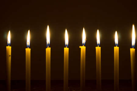 several glowing lights of candles brighten up in dark background.