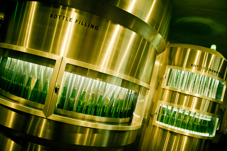 Green beer bottles being filled on production line in brewery