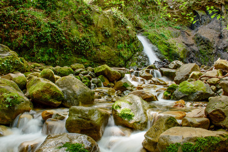 Attractive Waterfall with Green Moss Stone In Forest Stock Photo