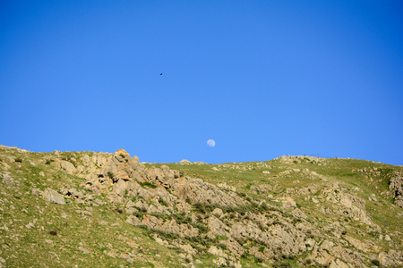Moon in Blue Sky Above Mountain in the Spring
