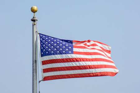 USA Flag Flying in the Wind under Blue Sky
