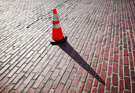 Traffic cone and long shadow on brick street Stock Photo