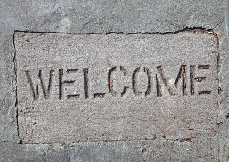 outline of welcome mat set in concrete