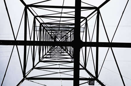 silhouette of high voltage electrical tower from below