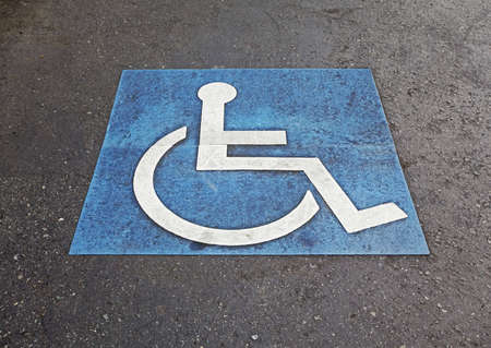 differently: international symbol of handicapped marking parking space Stock Photo