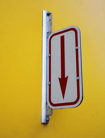 arrow sign on wall marking parking entrance