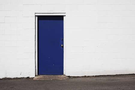 deep blue door on white building