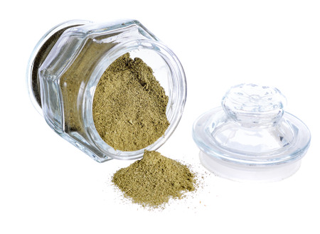 dried moringa powder  in glass jar on white background