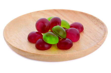 Gummy jelly apple and grape in wooden plate  isolated on white background Stock Photo