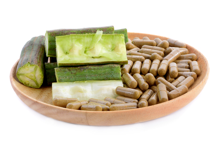 Moringa oleifera lam and Moring capsules  in wooden plate isolated on white background