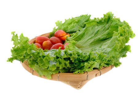 fresh lettuce leaves and tomatoes in basket isolated on white background