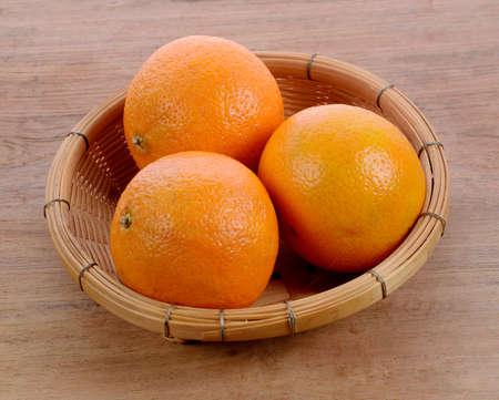 sweet ripe orange in bamboo basket  Isolated on wood table Stock fotó