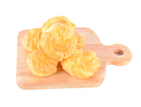 Cream puff with filling on wood isolated on white background
