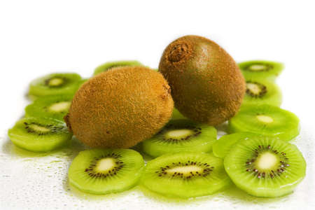 two kiwis amonst slices of kiwi