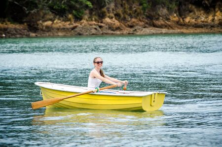 young woman rowing yellow dingy Imagens