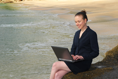 business woman on laptop at beach