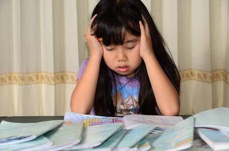 Little girl tired of doing homework photo