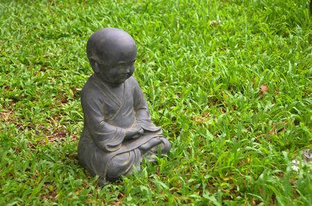 Black stone little buddha on green grass photo