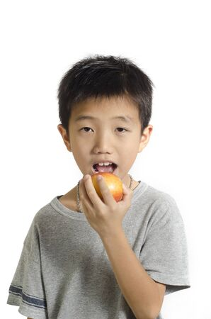 Small boy preparing to bite a big red apple isolated on white background photo