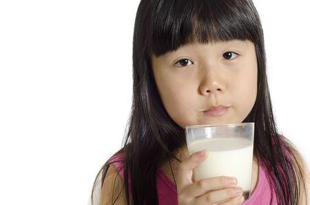 Cute little girl drinks milk, isolated over white Stock Photo - 10798215