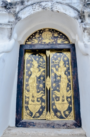 Traditional Thai art on a wood door in a temple photo