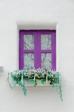Beautiful purple windows Greek Style on white wall photo