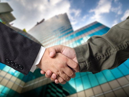 Business man and Engineer handshake with Building