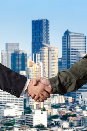 Business man and Engineer handshake with Building photo