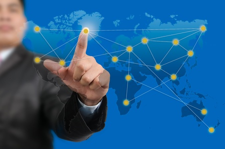 Businessman pressing on the world map network photo