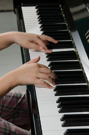Close up of childs hands playing the piano