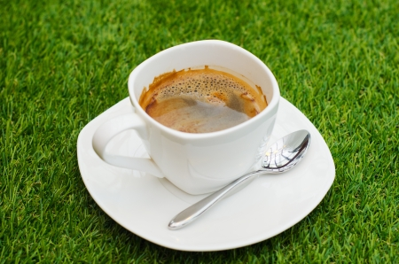 cup of coffee on green grass photo