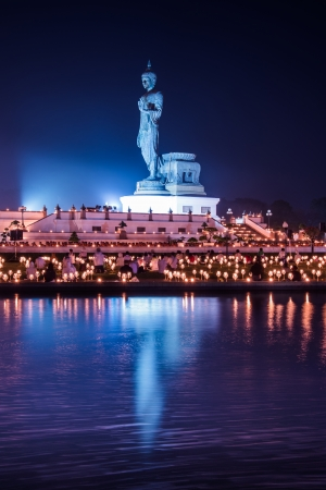 Candles light in hand of  Buddhist in twilight photo