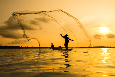 fishing nets: Silhouette of a fisherman throwing his net with sunset.