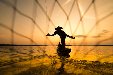 fish net: Silhouette of a fisherman throwing his net with sunset.