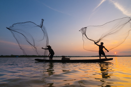 Silhouette of a fisherman throwing his net with sunset.