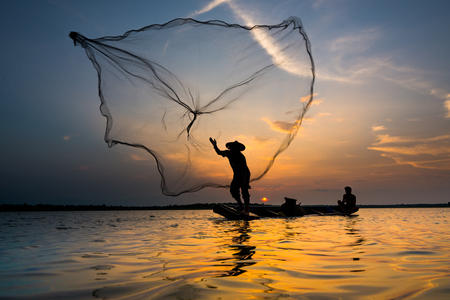 fishing catches: Silhouette of a fisherman throwing his net with sunset.