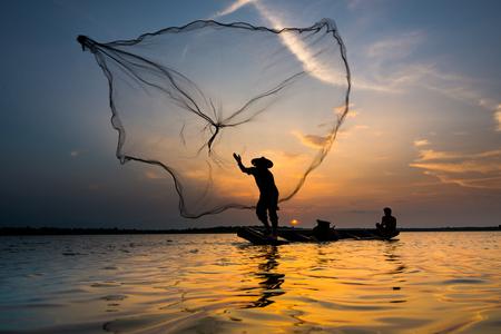 coger: Silueta de un pescador que lanza su red con la puesta del sol.