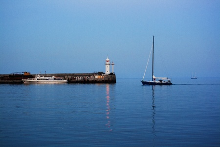 lighthouse and a sailboat in the dawn