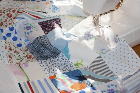 quilt: process of quilying onpatchwork blanket