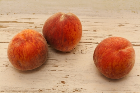 three ripe peaches on wooden surface photo