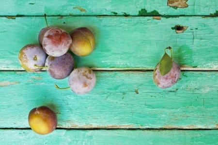 plums on old turquose color surface Foto de archivo